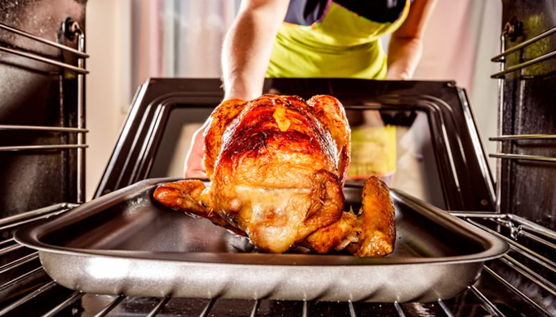 Woman putting a chicken in a clean oven